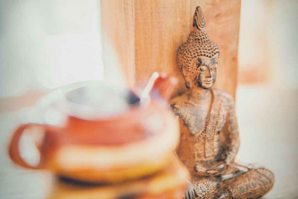 meditating buddha wooden statuette
